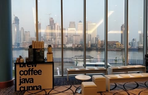 Coffee station placed by seating area in front of a large window overlooking a city
