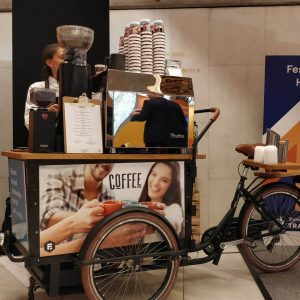 Barista stood by coffee bike at festival hall